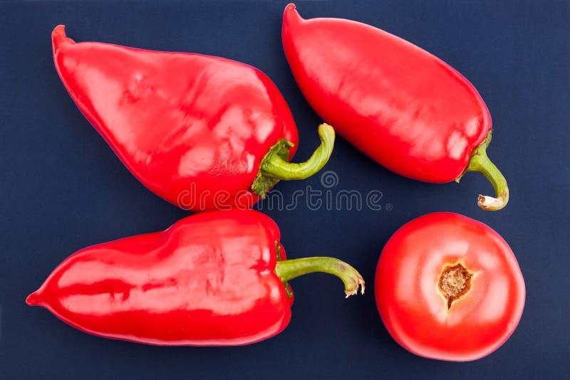 Tre ljusa stora röda spanska peppar och en röd tomatoe på den blåa closeupen för bästa sikt för bakgrund royaltyfri foto