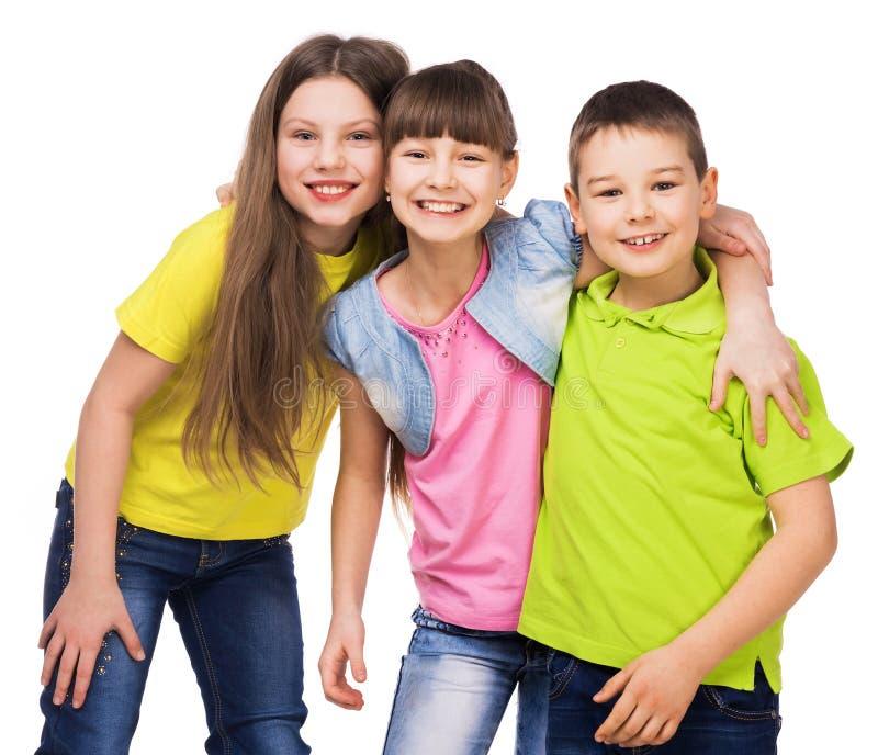 Tre lyckliga barn som embrasing sig royaltyfria bilder