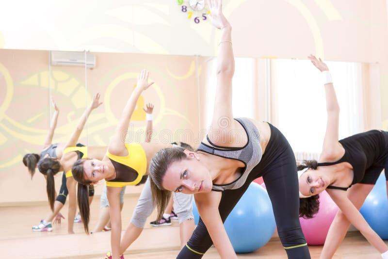 Tre lyckliga Caucasian kvinnliga idrottsman nen i godapassformen som har sträckning av övningar arkivfoto