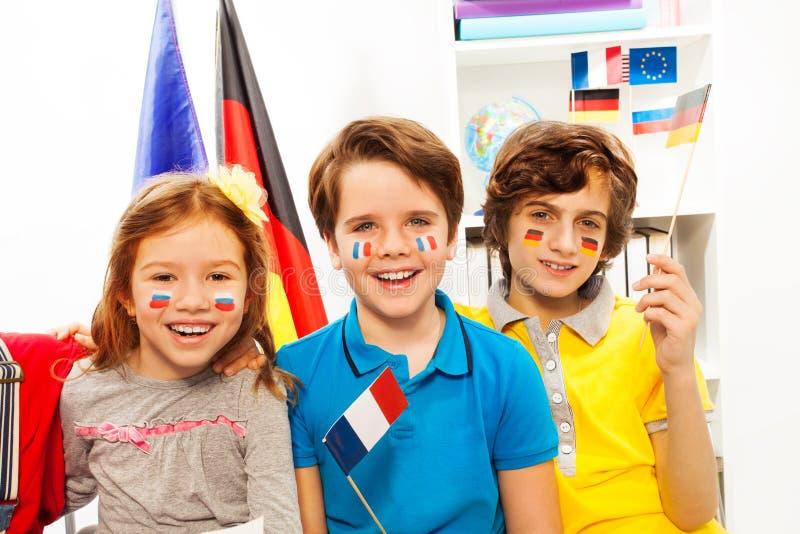 Tre lyckliga elever med flaggor på kinder på grupp royaltyfri foto