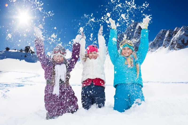 Tre lyckliga flickor som har gyckel med snö arkivbilder