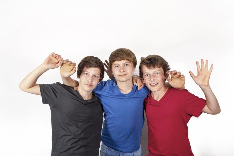 Tre lyckliga glade vänner i blått, rött och svart arkivfoton