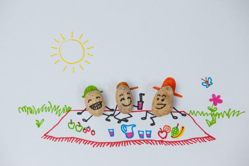 Tre lyckliga jordnötstatyetter har picknicken på en solig dag royaltyfria bilder