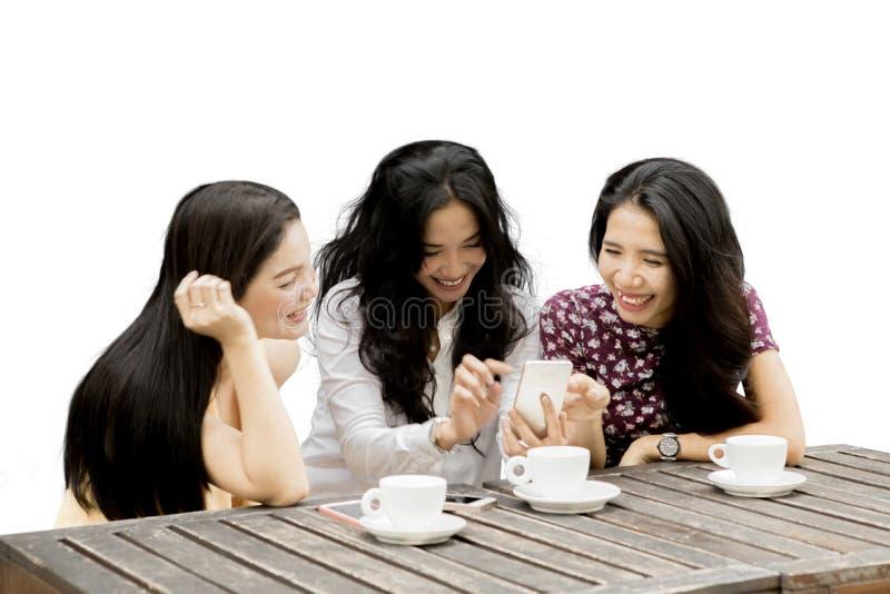 Tre lyckliga kvinnor med en mobiltelefon arkivbild