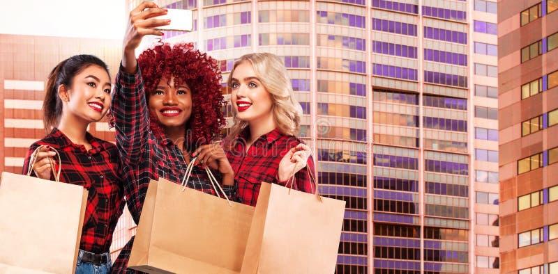Tre lyckliga kvinnor på shopping Afro- amerikan-, asiat- och caucasianlopp E Begrepp för säsongförsäljningar arkivfoton