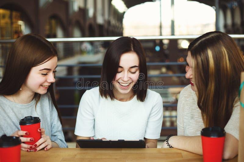 Tre lyckliga kvinnor som läser goda nyheter på minnestavlaPC:n arkivfoton