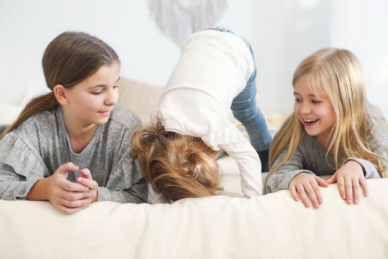 Tre lyckliga lilla systrar på en säng royaltyfria foton