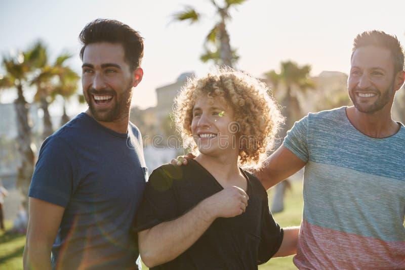 Tre lyckliga män som står yttersidan som tillsammans bort ser arkivbilder