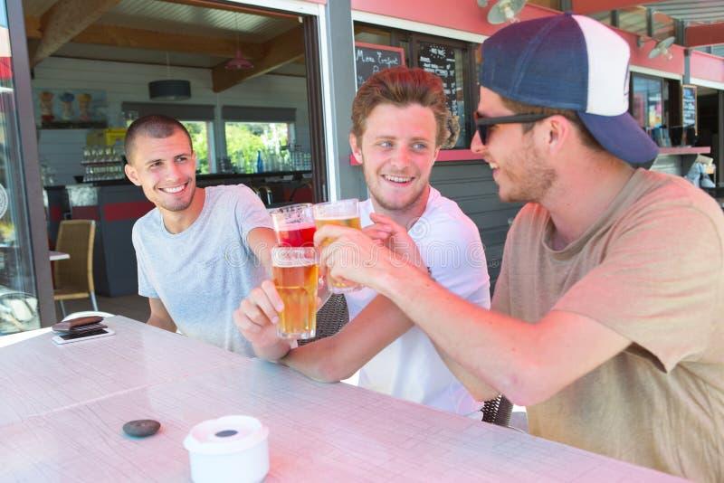 Tre lyckliga manliga vänner som dricker öl på restaurangterrassen arkivbild
