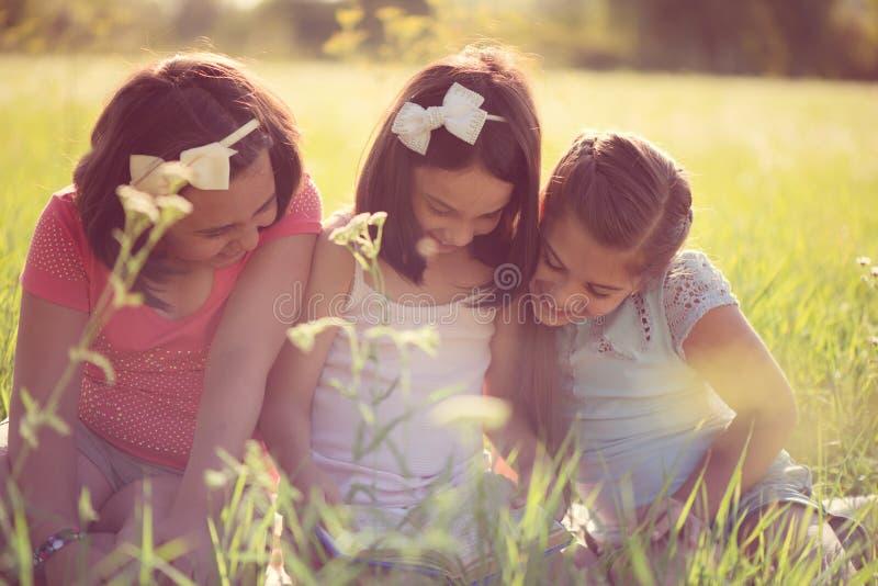 Tre lyckliga tonåriga flickor på parkerar royaltyfria foton