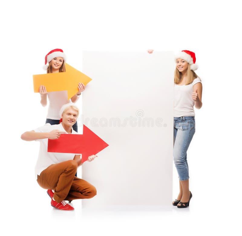 Tre lyckliga tonåringar i julhattar som pekar på ett baner royaltyfria foton