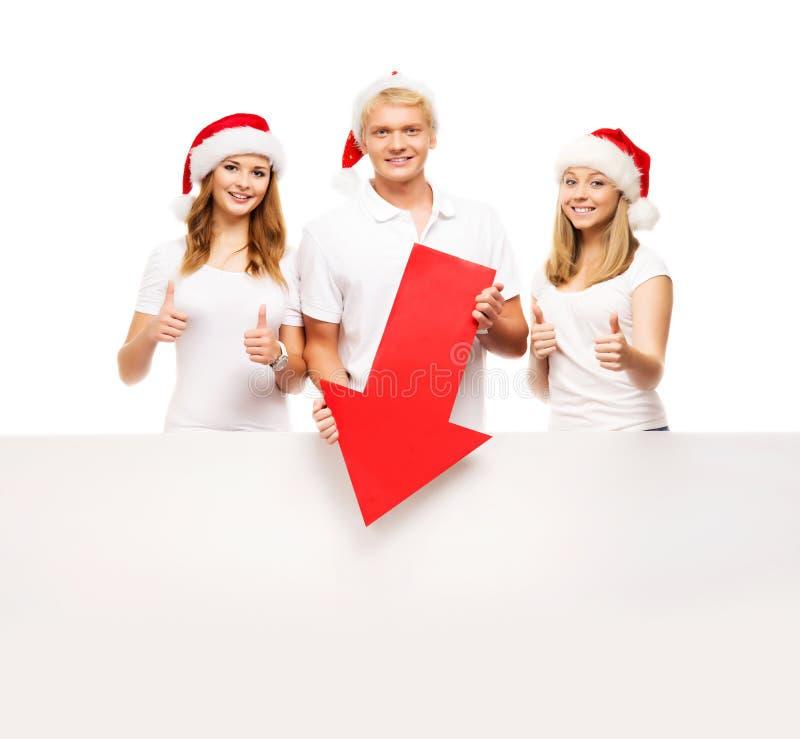 Tre lyckliga tonåringar i julhattar som pekar på ett baner fotografering för bildbyråer
