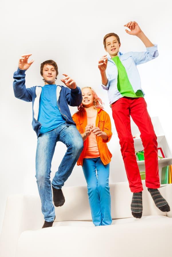 Tre lyckliga tonåringar som hoppar på den vita soffan royaltyfria bilder