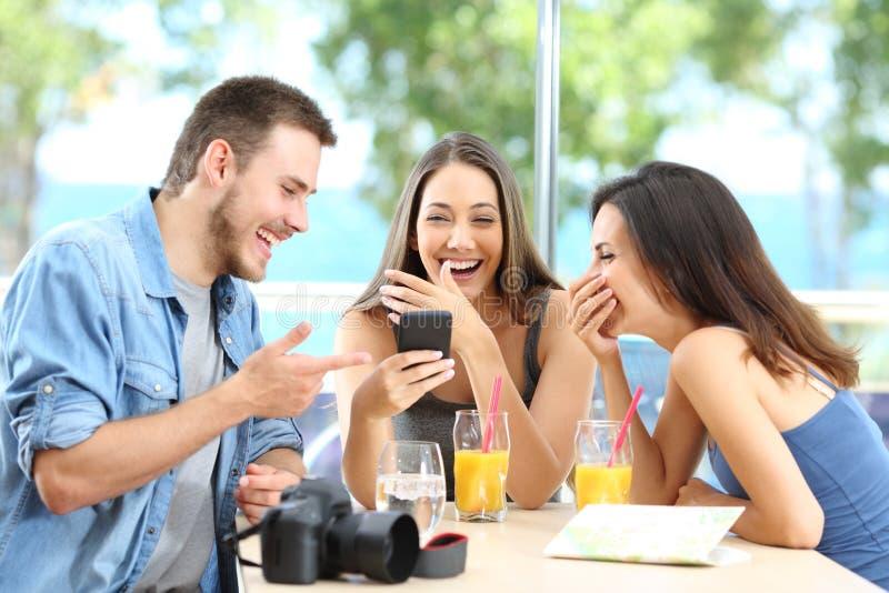 Tre lyckliga turister som skrattar tycka om semester royaltyfri fotografi