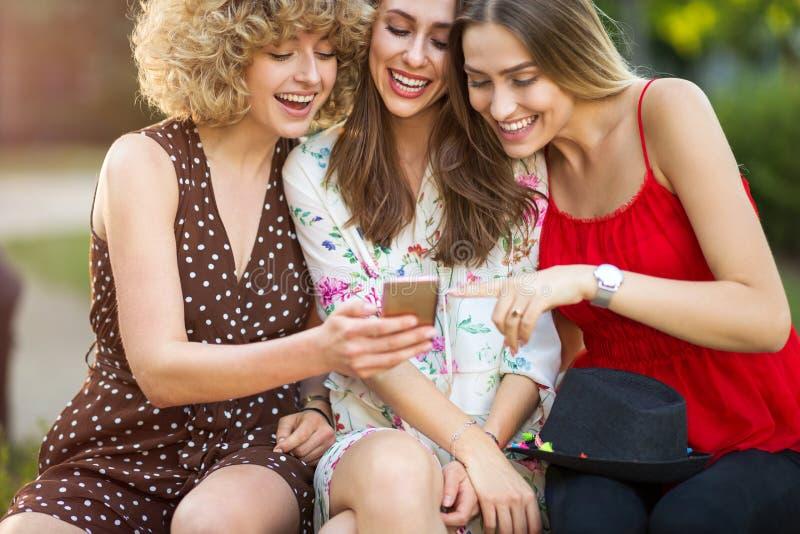 Tre lyckliga unga kvinnor som har gyckel med den smarta telefonen royaltyfri foto