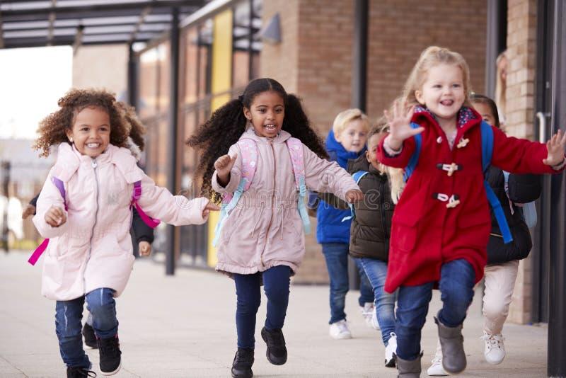 Tre lyckliga unga skolaflickor som bär lag och bär skolväskor som kör i en gångbana med deras klasskompisar utanför deras infa royaltyfri bild