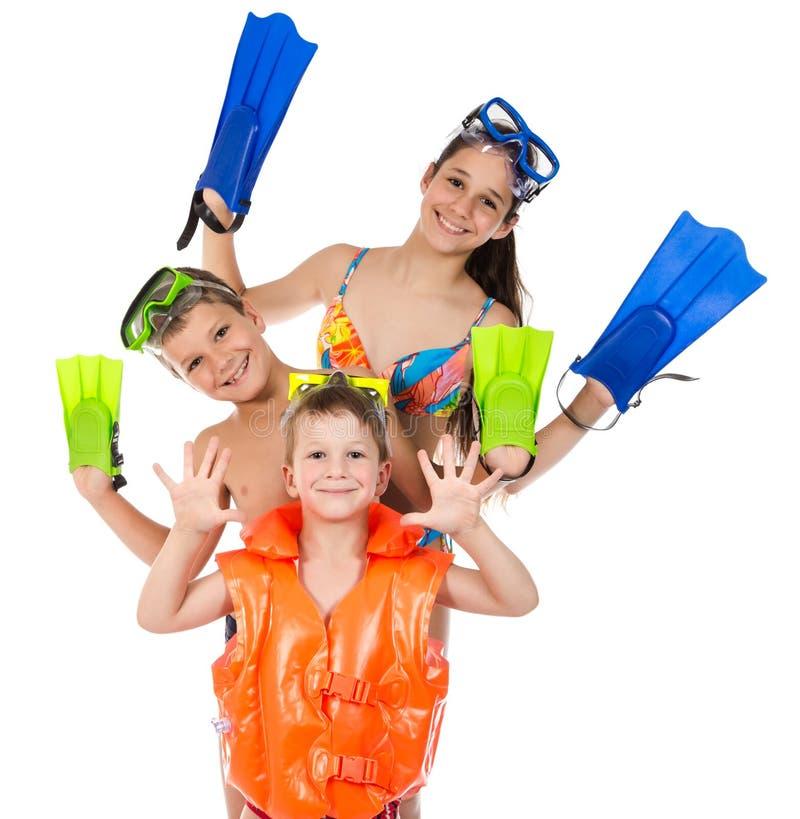 Tre lyckliga ungar i dykningmaskeringen som tillsammans står royaltyfria bilder