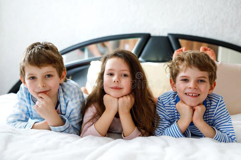 Tre lyckliga ungar i pyjamas som firar pajamapartiet Förträning och skolapojkar och flicka som har gyckel tillsammans arkivfoton