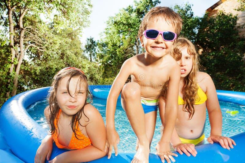 Tre lyckliga ungar som har gyckel i simbassäng royaltyfri bild