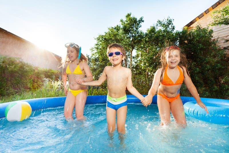 Tre lyckliga ungar som hoppar i simbassängen arkivfoton
