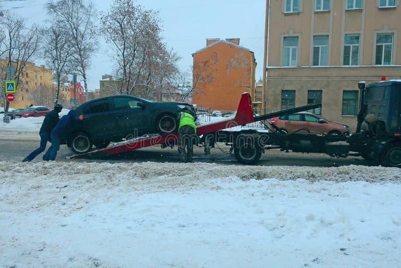 Tre män laddar en bil på en bärgningsbil royaltyfri bild