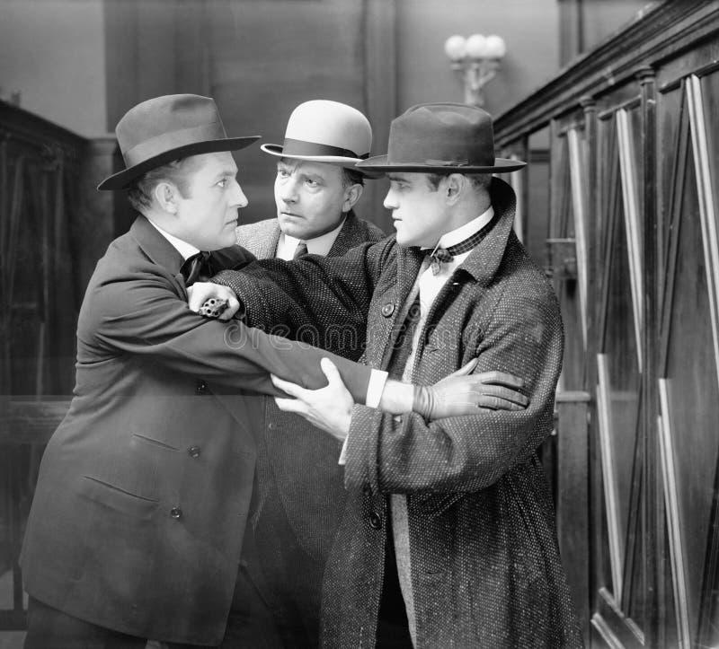Tre män som argumenterar med de (alla visade personer inte är längre uppehälle, och inget gods finns Leverantörgarantier som ther arkivbild