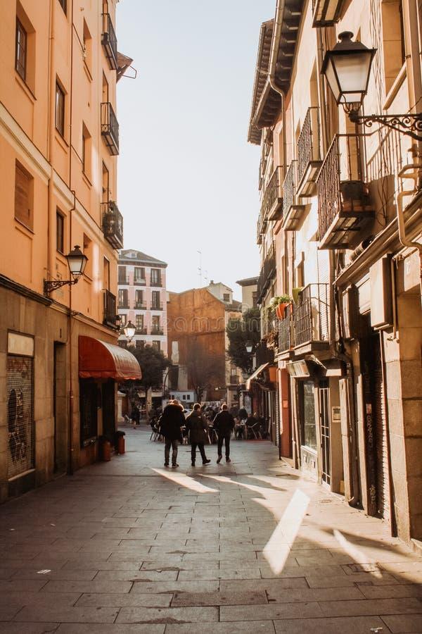 Tre män som går runt om Latinaen i Madrid Spanien på solnedgången arkivbilder