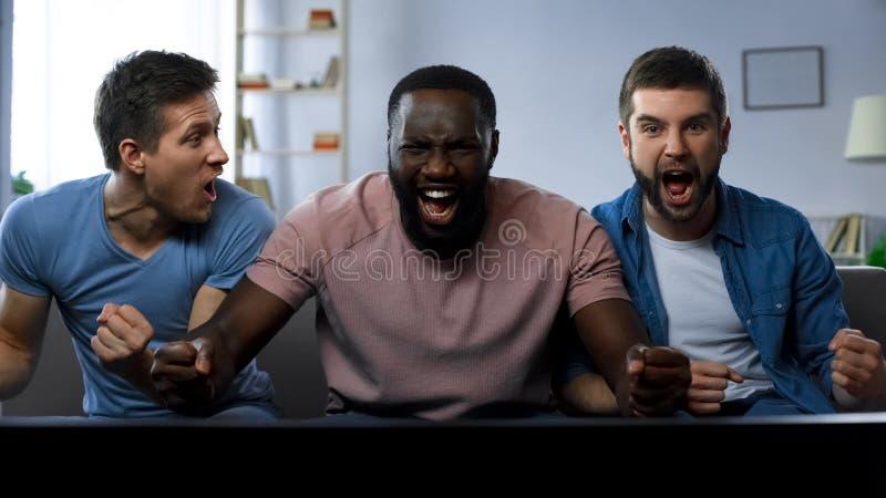 Tre män som håller ögonen på fotbollkonkurrens på den stora skärmen som hurrar det bästa fotbolllaget royaltyfria foton