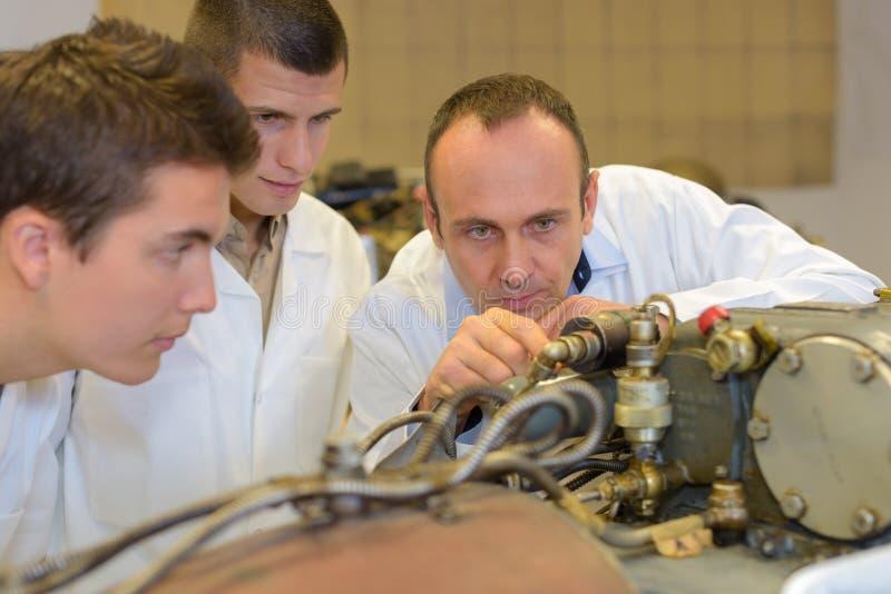 Tre män som ser teknikuppfinningen royaltyfri foto