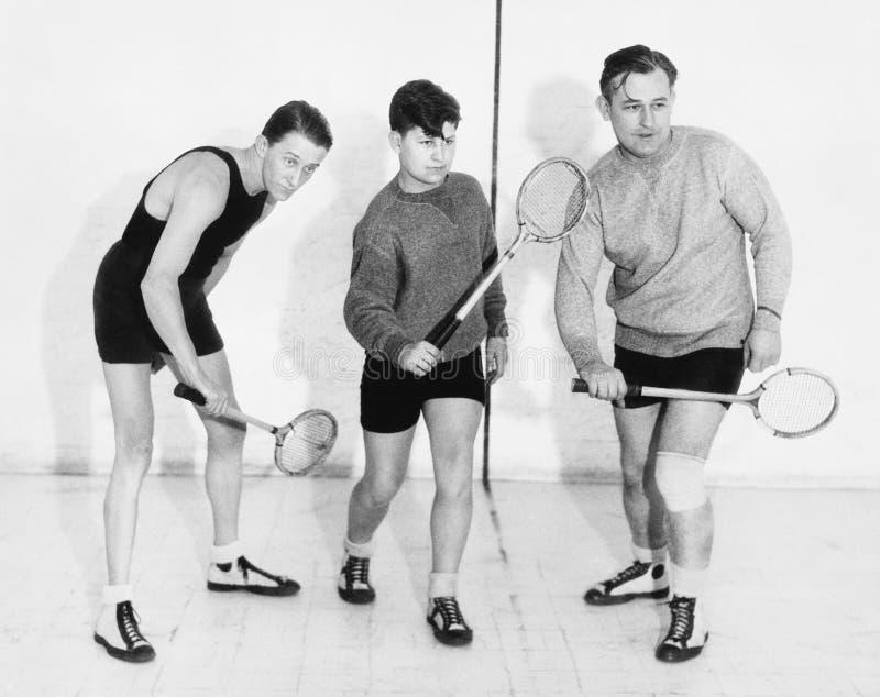 Tre män som spelar squash (alla visade personer inte är längre uppehälle, och inget gods finns Leverantörgarantier att det ska fi royaltyfri fotografi