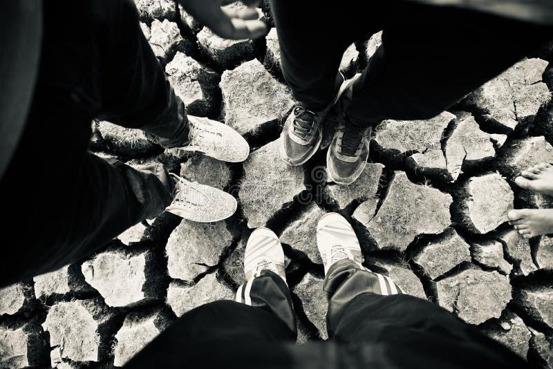 Tre män som står på sprucken jordyttersida arkivfoton