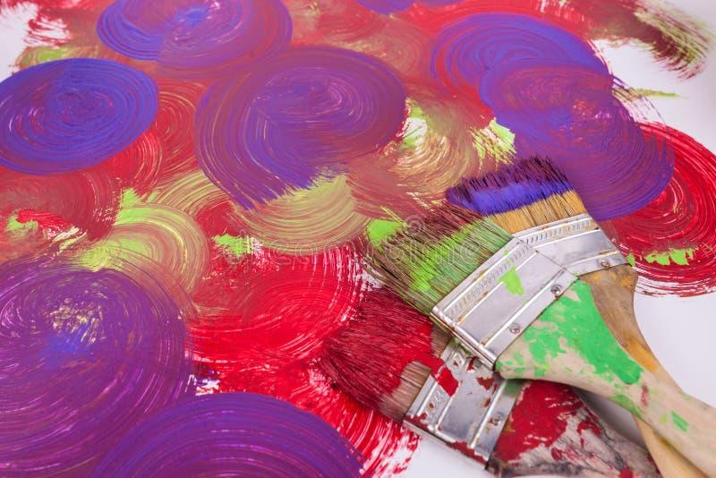 Tre målarfärgborstar målar virvlar i purpurfärgad röd gräsplan texturerad målad bakgrund arkivbild