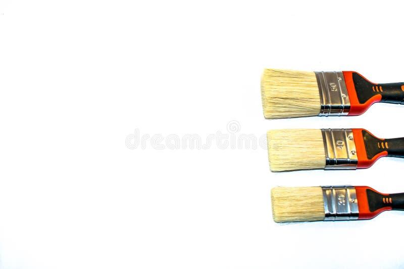 Tre målarpenslar som isoleras på en vit bakgrund arkivfoto