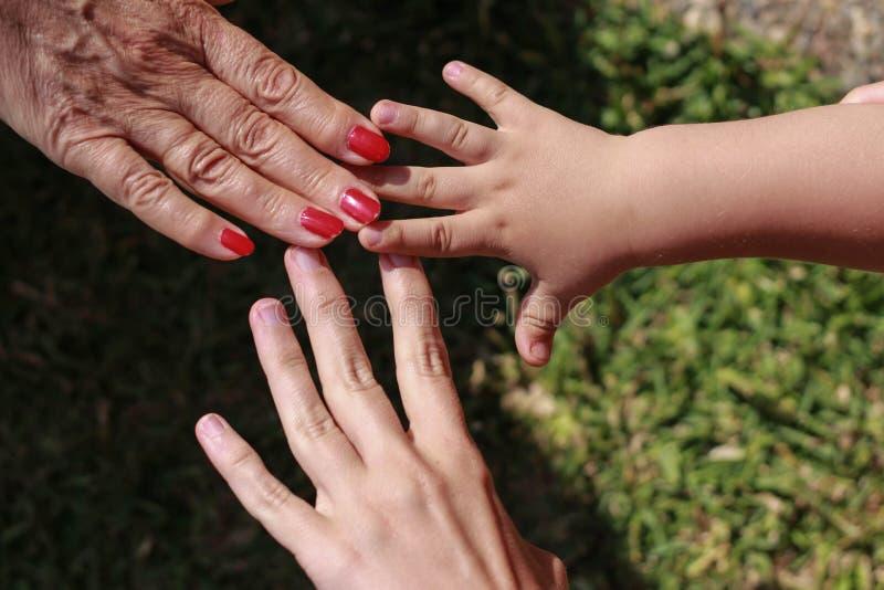 Tre mani della famiglia: figlio, madre e nonna immagini stock