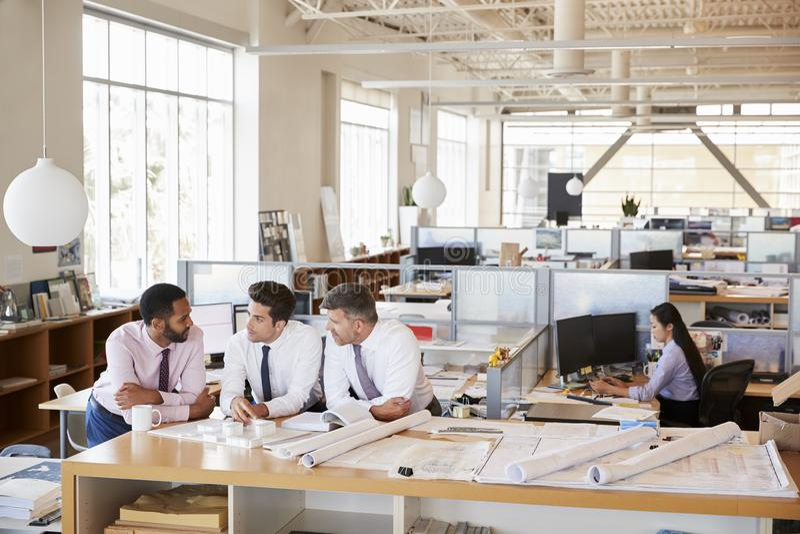 Tre manliga arkitekter i diskussion i ett öppet plankontor royaltyfri fotografi