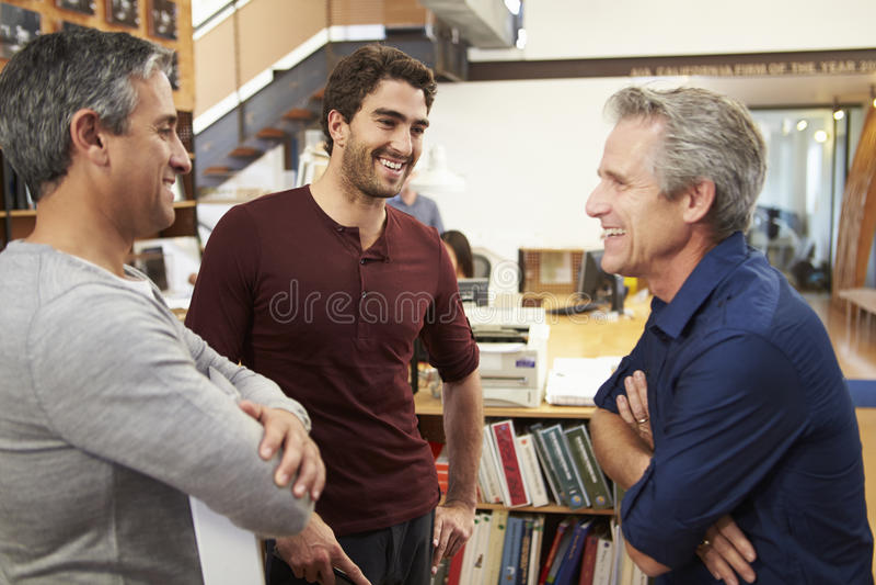 Tre manliga arkitekter som tillsammans pratar i modernt kontor royaltyfri bild