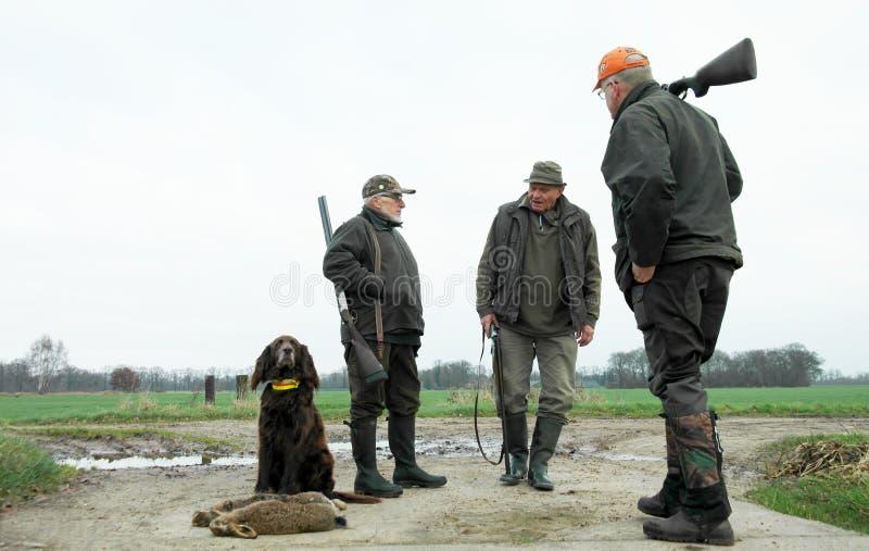 Tre manliga jägare och hund med hare lågt perspektiv lantligt område timmar liggandesäsongvinter Stolt sammanträde för jakthund m royaltyfri foto