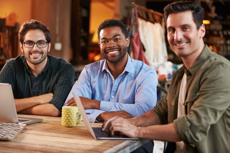 Tre manliga modeformgivare i möte genom att använda bärbara datorn royaltyfria foton