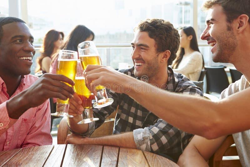 Tre manliga vänner som tycker om drinken på den utomhus- takstången arkivfoton