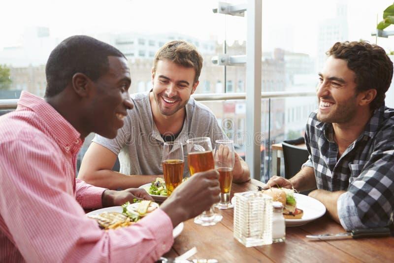 Tre manliga vänner som tycker om lunch på takrestaurangen arkivfoton