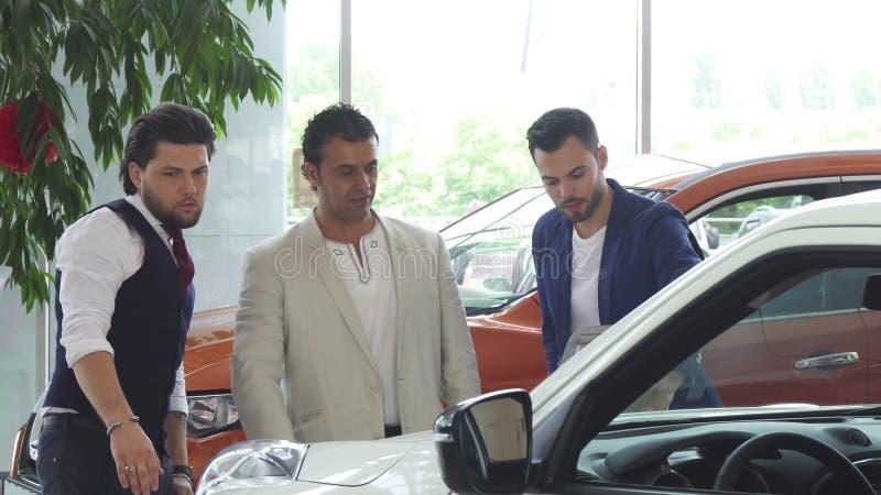Tre manliga vänner som undersöker bilen som är till salu på återförsäljaren arkivfoto