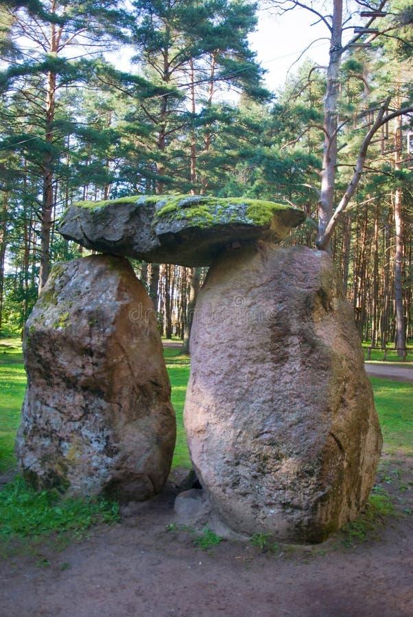Tre massi di pietra enormi sono impilati nella una figura in un coniferou immagini stock