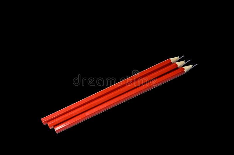 Tre matite in isolato su un fondo nero, colore rosso delle matite semplici della grafite fotografie stock libere da diritti