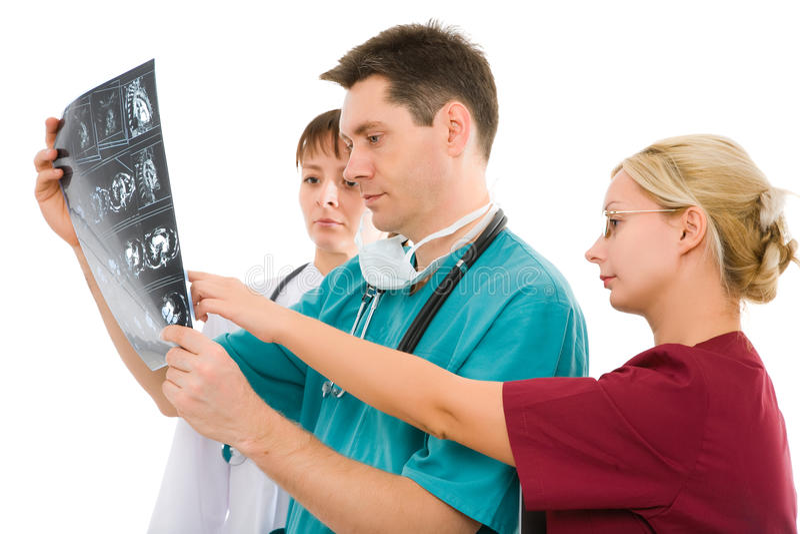 Tre medici con il tomogramma dei raggi X fotografia stock