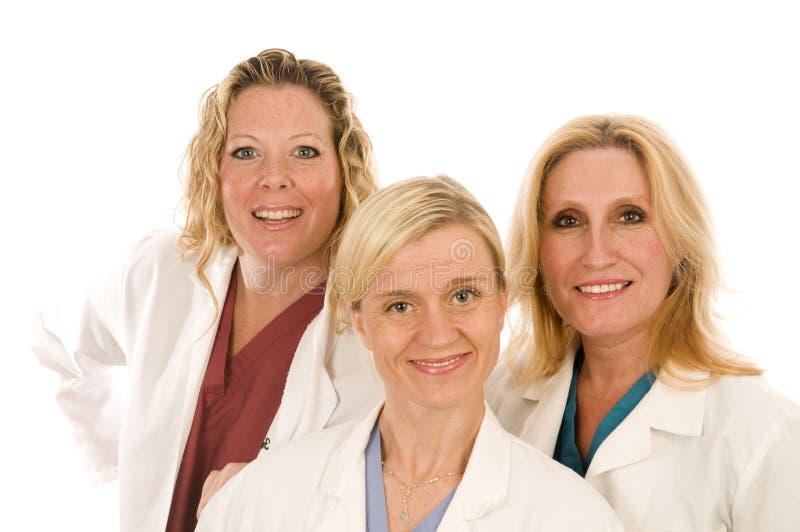 Tre medici o infermiere in cappotti del laboratorio medico immagine stock