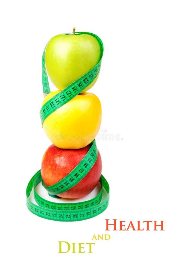 Tre mele con nastro adesivo di misurazione su un fondo bianco fotografia stock libera da diritti