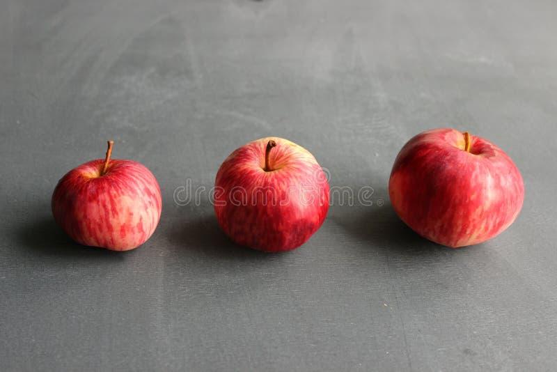 Tre mele rosse su una tabella di legno fotografia stock libera da diritti
