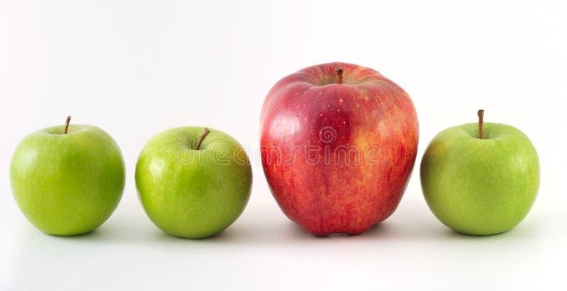 Tre mele verdi ed un colore rosso fotografia stock libera da diritti