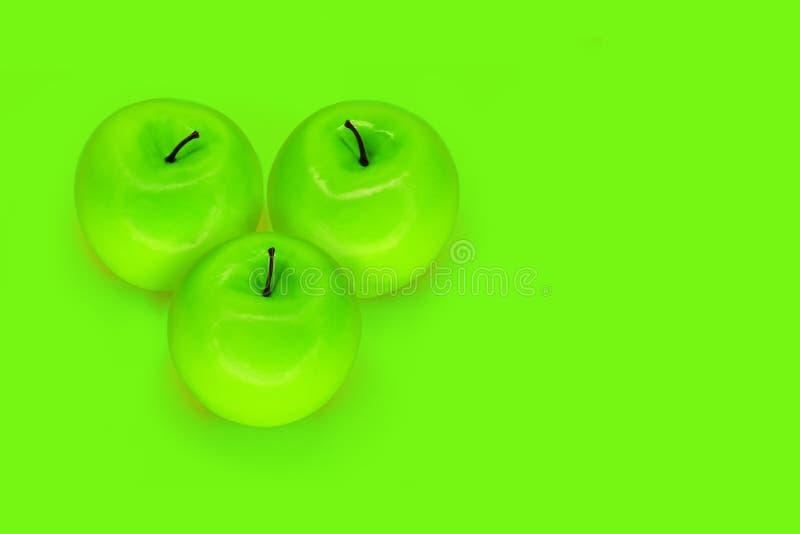 Tre mele verdi piegate sotto forma di un cuore su fondo verde con lo spazio della copia fotografia stock