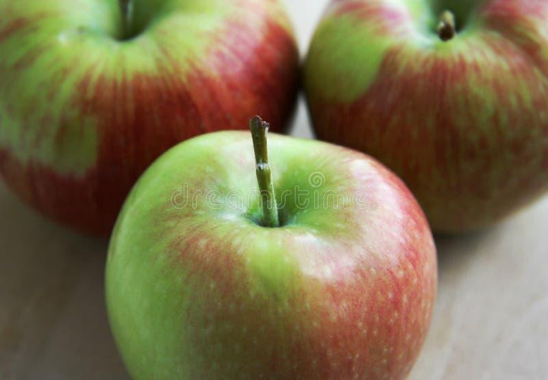 Tre mele verdi su legno immagini stock
